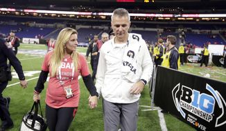 Ohio State head coach Urban Meyer walks off the field with his wife, Shelley Meyer, early Sunday, Dec. 2, 2018, after defeating Northwestern in the Big Ten championship NCAA college football game in Indianapolis. Ohio State won 45-24. (AP Photo/Michael Conroy)