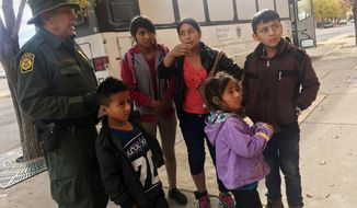 In this Thursday, Nov. 29, 2018, file photo, a migrant family from Central America waits outside the Annunciation House shelter in El Paso, Texas, after a U.S. Immigration and Customs Enforcement officer drops them off. (AP Photo/Russell Contreras) ** FILE **