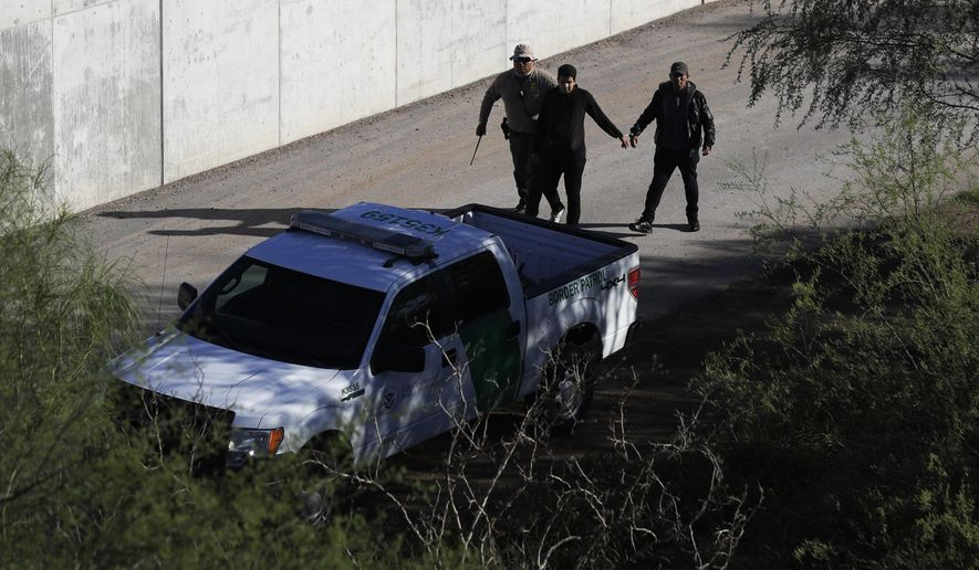 FILE - In this Nov. 16, 2016, file photo, a U.S. Customs and Border Patrol agent walks with suspected immigrants caught entering the country illegally along the Rio Grande in Hidalgo, Texas. While the Trump administration focuses attention on migrant caravans trying to cross the southern U.S. border in California, migration is surging at the opposite end of the border in South Texas. (AP Photo/Eric Gay, File)