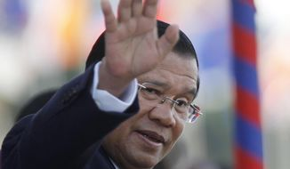 """FILE - In this Nov. 21, 2018, file photo, Cambodia's Prime Minister Hun Sen waves as he watches boat races during the water festival in Phnom Penh, Cambodia. Cambodia's parliament will consider legislation to allow politicians banned from political activity to have the ban lifted, a measure that long-serving Hun Sen's government is touting as a step """"to strengthen democracy and political space."""" (AP Photo/Heng Sinith, File)"""