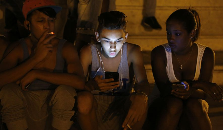 FILE - In this July 1, 2015 file photo, youths use a password protected wifi network coming from a five star hotel to surf the Internet on their smart phones in downtown Havana, Cuba. Cuba's government announced on Tuesday, Dec. 4, 2018 that its citizens will be offered full internet access on mobile phones starting Thursday, Dec. 6, becoming one of the last nations to do so. (AP Photo/Desmond Boylan, File)