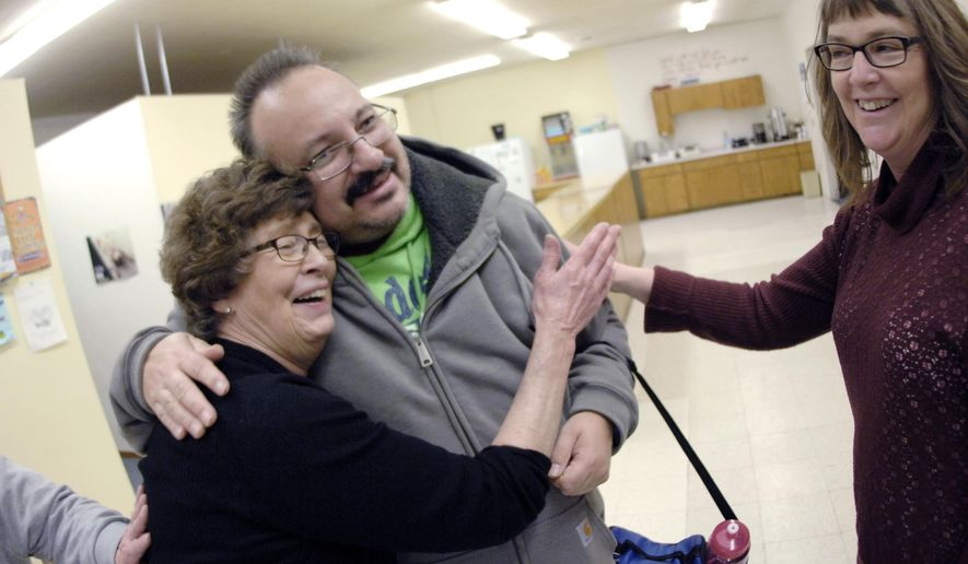 In this Nov. 25, 2018, photo, Leon Dietrich, one of the Charity Lutheran Church missionary outreach volunteers, is thanked by Linda Ault, left, and Patti Schmeichel before Dietrich and the other volunteers board the church back to Bismarck, N.D., after serving a post Thanksgiving Day meal at the Freedom Fellowship Church in McLaughlin, S.D. (Mike McCleary/The Bismarck Tribune via AP)