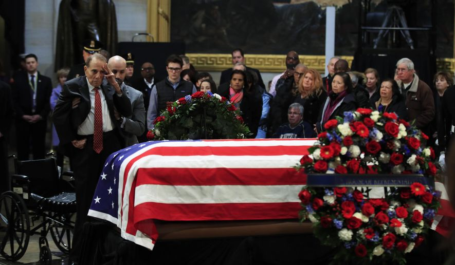 Former Sen. Bob Dole salutes the flag-draped casket containing the remains of former President George H.W. Bush as he lies in state at the U.S. Capitol in Washington, Tuesday, Dec. 4, 2018. (AP Photo/Manuel Balce Ceneta)