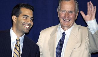 FILE - In this Aug. 31, 2004 file photo. George P. Bush, left, stands hands with his grandfather, former President George H.W. Bush in New York prior to their remarks at a reception hosted by the Hispanic Alliance for Progress Institute in conjunction with the Republican National Convention. George H.W. Bush's political career spanned a generation and straddled the America before and after Jim Crow but also was a key figure in the GOP as reaching out to Latino voters. (AP Photo/Ted S. Warren, File)