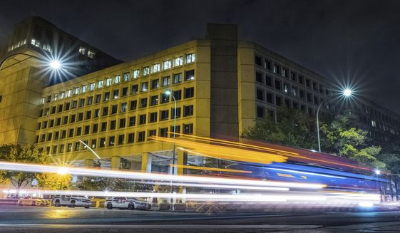 In this Nov. 1, 2017, file photo, traffic along Pennsylvania Avenue in Washington streaks past the Federal Bureau of Investigation headquarters building.  (AP Photo/J. David Ake) **FILE**
