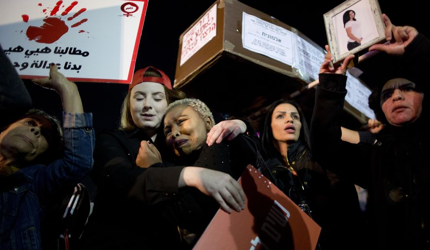 Women attend a protest against violence against women in Tel Aviv, Israel, Tuesday, Dec. 4, 2018. A nationwide strike in protest of violence against women and commemorating the 24 victims of domestic violence with thousands of men and women calling on the government to take action against domestic abuse. (AP Photo/Oded Balilty)