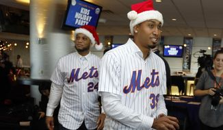 Robinson Cano, left, and Edwin Diaz wear Santa hats as they arrive to participate in the New York Mets annual Kids Holiday Party, at CitiField, in New York, Tuesday, Dec. 4, 2018. The Mets acquired eight-time All-Star second baseman Robinson Cano and major league saves leader Edwin Diaz from the Seattle Mariners in a seven-player trade Monday. (AP Photo/Richard Drew)