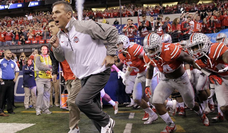 FILE - In this Dec. 6, 2014 file photo, Ohio State head coach Urban Meyer runs onto the field with his team at the start of the Big Ten Conference championship NCAA college football game against Wisconsin, in Indianapolis. Ohio State says Urban Meyer will retire after the Rose Bowl and assistant Ryan Day will be the next head coach.After seven years and a national championship at Ohio State, the 54-year-old Meyer will formally announce his departure Tuesday, Dec. 4, 2018, at a news conference. (AP Photo/Darron Cummings, File)