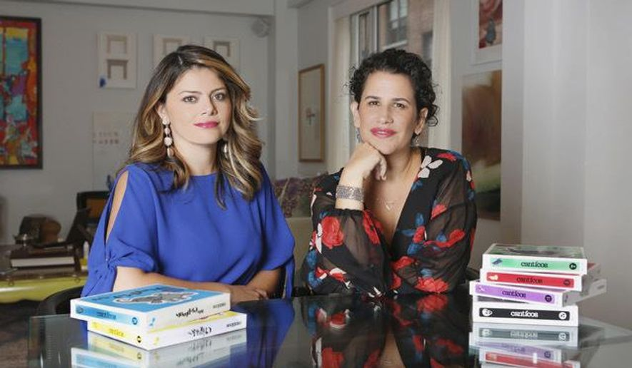 In this undated photo provided by Creation Studios, Nuria Santamaria Wolfe, left, and Susie Jaramillo, right, co-founders of family-owned entertainment company Encantos Media Studios, pose for a photo with their series of bilingual nursery rhyme books, Canticos. (Lara Alcantara/Creation Studios via AP)