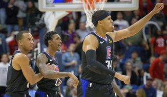 Los Angeles Clippers guard Lou Williams (23) is congratulated by guard Avery Bradley (11) as forward Tobias Harris (34) celebrates the two point basket late in the game to give the Clippers a lead against the New Orleans Pelicans in the second half of an NBA basketball game in New Orleans, La. Monday, Dec. 3, 2018. (AP Photo/Matthew Hinton)