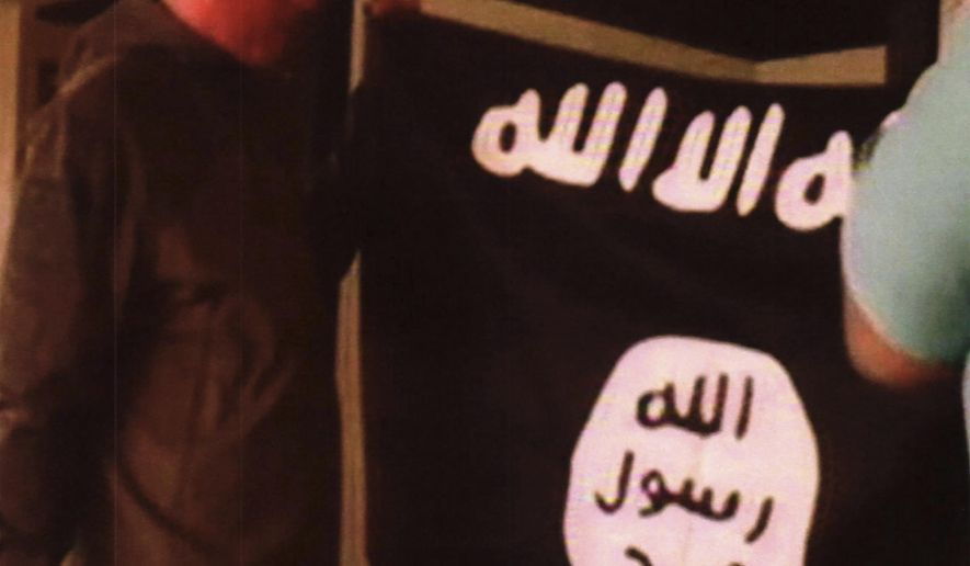 FILE - In this undated file image taken from FBI video and provided by the U.S. Attorney's Office in Hawaii on Thursday, July 13, 2017, Army Sgt. 1st Class Ikaika Kang holds an Islamic State group flag after allegedly pledging allegiance to the group at a house in Honolulu. On Tuesday, Dec. 4, 2018, Kang is scheduled to be sentenced for trying to help the Islamic State group. (FBI/U.S Attorney's Office, District of Hawaii via AP, File)