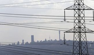 FILE - In this Tuesday, March 10, 2015 file photo, electricity pylons cross the skyline of Johannesburg city, background. South Africa's troubled power utility has been implementing a series of power cuts nationwide, intensifying concern about attempts to spur growth in one of Africa's biggest economies. (AP Photo/Themba Hadebe, File)