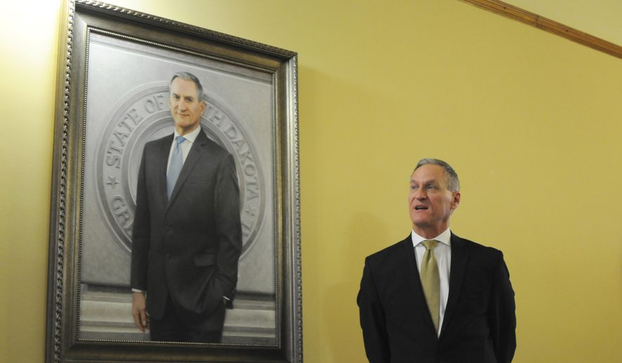 Gov. Dennis Daugaard speaks during the unveiling of his official Capitol portrait in Pierre, S.D., Tuesday, Dec. 4, 2018. Connecticut artist Susan Booke Durkee painted the portrait after being chosen through a national selection process. (AP Photo/James Nord)