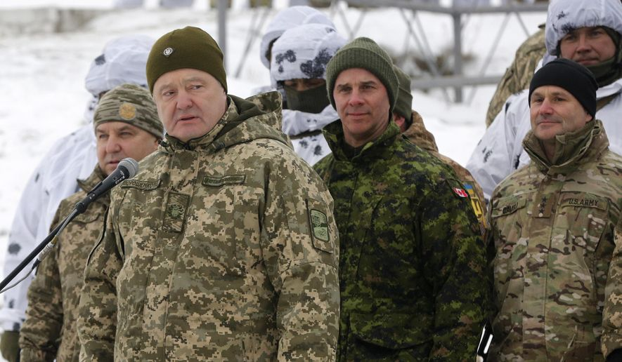 Ukrainian President Petro Poroshenko, second left, addresses Ukrainian soldiers as Canadian Army Lieutenant General Jean-Marc Lanthier stands at center, and commander of U.S. Army in Europe Christopher Cavoli stands right, during military drills in base Honcharivske, Chernihiv region, Ukraine, Monday, Dec. 3, 2018. Ukraine's president announced a partial call-up of reservists for training amid tensions with Russia, saying Monday that the country needs to beef up its defenses to counter the threat of a Russian invasion. (AP Photo/Efrem Lukatsky)