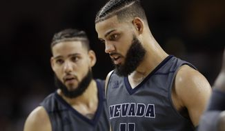 In this Saturday, Dec. 1, 2018 photo, Nevada 's Cody Martin, right, stands in front of his twin brother Caleb Martin during the second half of an NCAA college basketball game against Southern California in Los Angeles. No. 6 Nevada has matched its 8-0 start from last season, winning its games by an average of 20 points.(AP Photo/Marcio Jose Sanchez)