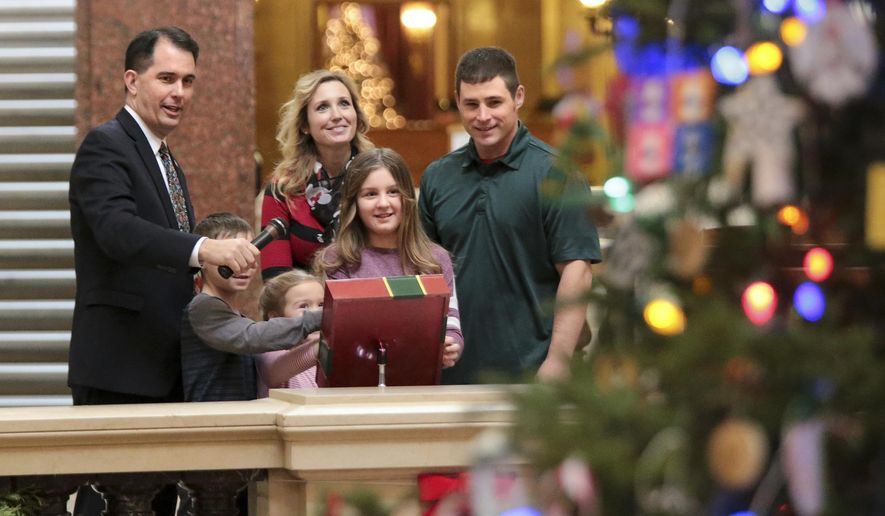 Wisconsin Gov. Scott Walker, left, with the help of the Mary and Don Miller family from Plainfield, Wis., flipped the switch to light the state Christmas Tree in the Capitol Rotunda, Tuesday, Dec. 4, 2018 at the Capitol in Madison, Wis. The Senate and Assembly are set to send dozens of changes in state law to Walker's desk Tuesday. (Steve Apps/Wisconsin State Journal via AP)
