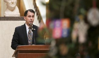 Wisconsin Gov. Scott Walker speaks during the lighting of the state Christmas Tree in the Capitol Rotunda, Tuesday, Dec. 4, 2018, at the Capitol in Madison, Wis. The Senate and Assembly are set to send dozens of changes in state law to Walker's desk Tuesday. (Steve Apps/Wisconsin State Journal via AP)