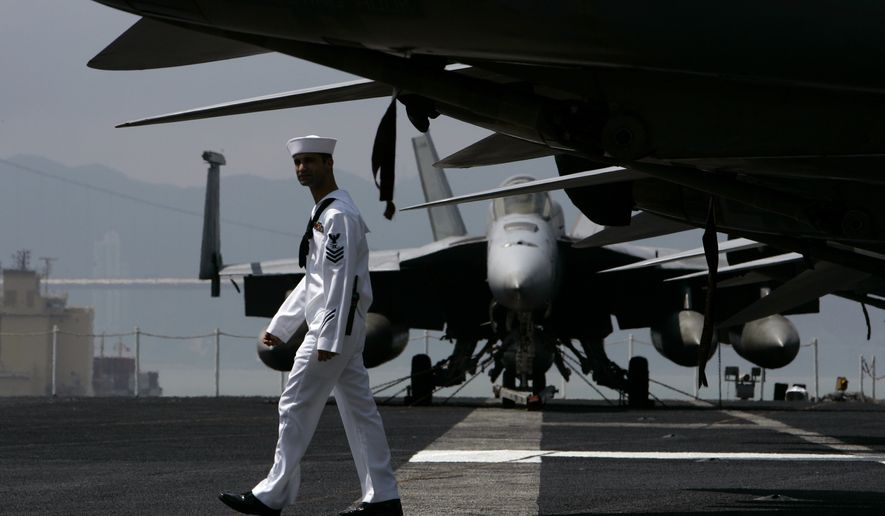 A U.S. Navy sailor walks beside FA-18 fighter jets aboard the USS Ronald Reagan aircraft carrier in Hong Kong Thursday, June 19, 2008. The USS Ronald Reagan is currently visiting Hong Kong for a port visit. (AP Photo/Kin Cheung)