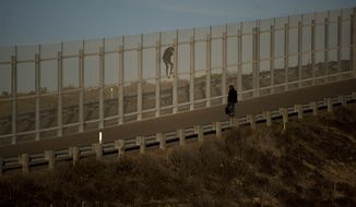 In a photo taken from the Tijuana, Mexico, side of the border, two immigrants on U.S. soil try to jump the second wall before border police arrived and arrested them, Sunday, Dec. 2, 2018. Thousands of migrants who traveled via caravan are seeking asylum in the U.S., but face a decision between waiting months or crossing illegally, because the U.S. government only processes a limited number of cases a day at the San Ysidro border crossing in San Diego. (AP Photo/Ramon Espinosa)