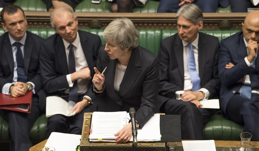 Britain's Prime Minister Theresa May, centre, gives a reply to lawmakers during the scheduled Prime Minister's Questions time, in the House of Commons, London, Wednesday Dec. 5, 2018. Britains House of Commons opened round two Wednesday in a bruising battle between lawmakers and Prime Minister Theresa May's government over Britain's Brexit split with the EU. (UK Parliament, Mark Duffy via AP)