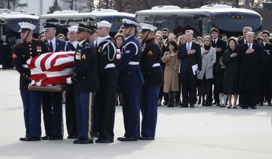 Former President George W. Bush watches as the flag-draped casket of former President George H.W. Bush is carried by a joint services military honor guard to Special Air Mission 41, Wednesday, Dec. 5, 2018, at Andrews Air Force Base, Md. (AP Photo/Alex Brandon, Pool)