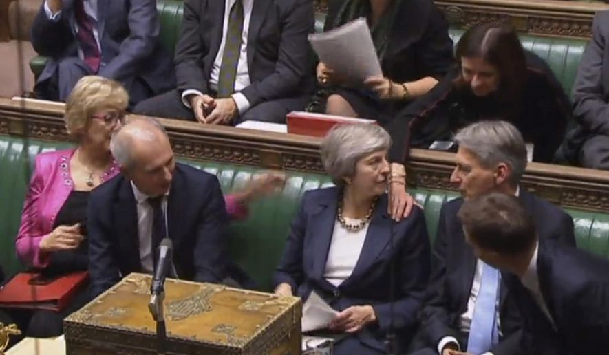 Britain's Prime Minister Theresa May Prime Minister Theresa May is congratulated by Conservative Party ministers in the House of Commons after speaking at the start of a five-day debate on the Brexit European Union Withdrawal Agreement, Tuesday Dec. 4, 2018. The British government received a historic rebuke from lawmakers on Tuesday over its Brexit plans, an inauspicious sign for Prime Minister Theresa May as she opened an epic debate in Parliament that will decide the fate of her Brexit divorce deal with the European Union. (Parliament TV/PA via AP)