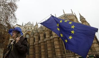 An Anti Brexit campaigner waves a European Union flag in Westminster in London, Tuesday, Dec. 4, 2018. Britain's Prime Minister Theresa May is due to address Parliament Tuesday, opening five days of debate before a Dec. 11 vote on the divorce agreement.(AP Photo/Kirsty Wigglesworth)