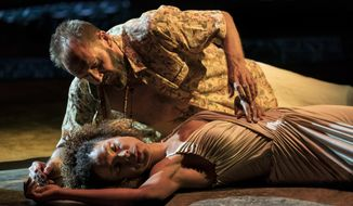 In this undated photo released by The National Theatre, a scene from the London National Theatre production of Antony & Cleopatra starring Ralph Finnes, top, and Sophie Okonedo, starring as the lovers rocked by war and empire. The tale of a tragic romance by William Shakespeare, directed by Simon Godwin, has two top-flight actors and a live snake, no wonder it's a hit show. (Johan Persson/National Theatre via AP)