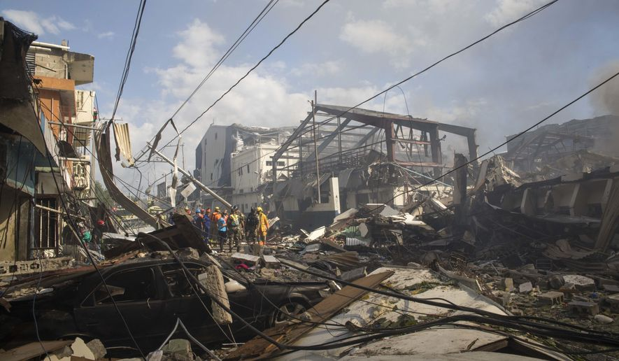 Search and rescue stand in the debris caused by an explosion at the Polyplas plant in the Villas Agricolas neighborhood in Santo Domingo, Dominican Republic, Wednesday, Dec. 5, 2018. The mayor told reporters the fire began when a boiler exploded early Wednesday afternoon at the plastics company. Authorities say at least two people have died. (AP Photo/Tatiana Fernandez)