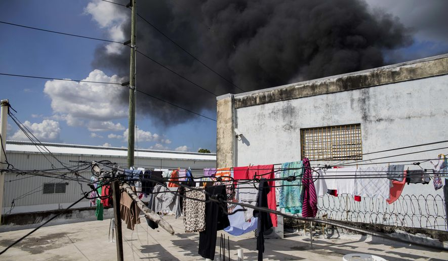 A black plume of smoke rises after an explosion at the Polyplas plant in the Villas Agricolas neighborhood in Santo Domingo, Dominican Republic, Wednesday, Dec. 5, 2018. The mayor told reporters the fire began when a boiler exploded early Wednesday afternoon at the plastics company. Authorities say at least two people have died. (AP Photo/Tatiana Fernandez)