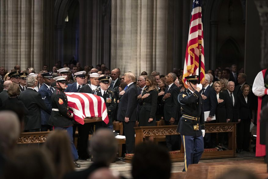 The flag-draped casket of former President George H.W. Bush is carried by a military honor guard past former President George W. Bush, left side, President Donald Trump, first lady Melania Trump, former President Barack Obama, Michelle Obama, former President Bill Clinton, former Secretary of State Hillary Clinton, former President Jimmy Carter, and Rosalynn Carter during a State Funeral at the National Cathedral, Wednesday, Dec. 5, 2018, in Washington. (AP Photo/Alex Brandon, Pool)