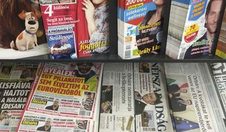 FILE - In this file photo dated Saturday, Oct. 8, 2016, a newsstand including Saturday papers with Nepszabadsag daily is pictured in Budapest, Hungary.  The creation in Hungary of a giant, pro-government media conglomerate will not have to be scrutinized by media or competition authorities as the order published Wednesday Dec. 5, 2018, is signed by Prime Minister Viktor Orban. (AP Photo/Andras Nagy, FILE)