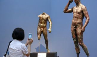 """In this Monday, July 27, 2015 photo, reporter Sookee Chung takes a photo of a sculpture titled """"Statue of a Victorious Youth, 300-100 B.C."""" at the J. Paul Getty Museum in Los Angeles. The J. Paul Getty Museum in Los Angeles has vowed to assert its right to keep an important Greek statue after Italy's highest court rejected its appeal of a ruling ordering the artwork to be returned to Italy. The ANSA news agency said Tuesday that the Court of Cassation rejected the appeal outright earlier this week. """"Victorious Youth,"""" a nearly life-sized bronze dating from 300 B.C. to 100 B.C., is one of the highlights of the Getty collection. (AP Photo/Nick Ut, File )"""