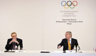 International Olympic Committee (IOC) President Thomas Bach, right, gestures to John Coates, left, chairman of the IOC Coordination Commission for the 2020 Tokyo Olympics and Paralympics, shake hands prior to an IOC Executive Board meeting Saturday, Dec. 1, 2018, in Tokyo. The IOC said boxing will take place at the 2020 Tokyo Olympics. But exactly who runs the tournament and the details of qualifying are up in the air because of charges of corruption and malfeasance surrounding the boxing federation that runs the sport at the Olympics. (AP Photo/Eugene Hoshiko)