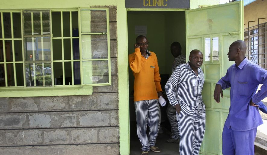 In this photo taken Wednesday, Oct. 31, 2018, prisoner Gibson Makini, 40, center, who aids his fellow inmates in writing legal documents, stands with them in Naivasha Prison in Kenya. Many prisoners are illiterate and poor, with little resources to fight for themselves, but the African Prisons Project is helping some to master basic literacy and study law, turning them into their own legal advocates in countries where such assistance is desperately rare. (AP Photo/Josphat Kasire)