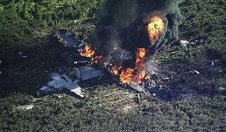 FILE - In this July 10, 2017, file image made from video provided by WLBT-TV, smoke and flames rise from a military plane that crashed in a farm field in Itta Bena, Miss. Investigators say bad maintenance practices at a Georgia air force base missed a deteriorating propeller blade that broke off six years later as a U.S. Marine Corps transport plane cruised over Mississippi at 20,000 feet, causing the KC-130T to break into pieces and plunge into a soybean field, killing 15 Marines and a Navy corpsman, according to the report on the causes of the July 10, 2017, crash, released Wednesday, Dec. 5, 2018. (WLBT-TV via AP, File)