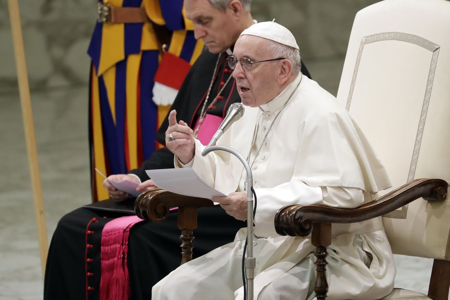 Pope Francis, flanked by Vatican Prefect of the Pontifical Household, Archbishop Georg Ganswein, delivers his message during a weekly general audience, in the Pope Paul VI hall, at the Vatican, Wednesday, Dec. 5, 2018. (AP Photo/Andrew Medichini)