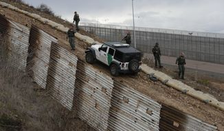 U.S. border patrol agents standing in San Ysidro, California leave after responding to at least two men on the Mexican side of the U.S. border wall, one with his face covered and another holding rocks, in Tijuana, Mexico, Thursday, Dec. 6, 2018. The incident diffused soon after and the agents left. (AP Photo/Rebecca Blackwell)