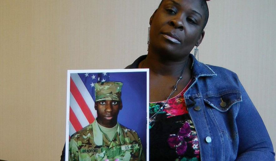 """FILE - In this Nov. 27, 2018, file frame from video, April Pipkins holds a photograph of her deceased son, Emantic """"EJ"""" Bradford Jr., during an interview in Birmingham, Ala. Bradford, who was licensed to carry a gun, was killed Thanksgiving night by an officer responding to a report of gunfire at a shopping mall in Hoover, Ala. The recent shootings of Bradford Jr. and Jemel Roberson amplified long-held worries that bad things can happen when a black man is seen with a gun. (AP Photo/Jay Reeves, File)"""