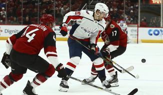 Washington Capitals center Lars Eller (20) tries to control the puck between Arizona Coyotes defenseman Kevin Connauton (44) and center Alex Galchenyuk (17) during the first period of an NHL hockey game Thursday, Dec. 6, 2018, in Glendale, Ariz. (AP Photo/Ross D. Franklin)