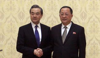 In this May 2, 2018, file photo, North Korean Foreign Minister Ri Yong-ho, right, poses with his Chinese counterpart Wang Yi at the Mansudae Assembly Hall in Pyongyang, North Korea. North Korea is sending its foreign minister to key ally China for talks amid a stall in efforts to persuade Pyongyang to dismantle its nuclear programs. Ri was due to arrive late Thursday, Dec. 6, 2018, and meet Friday, Dec. 7 with Wang. (AP Photo/Jon Chol Jin, File)