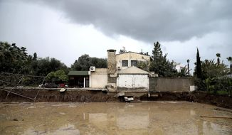 A house is seen by flooded area after heavy rain overnight near Kerynia city in the Turkish Cypriots breakaway north part of Cyprus, Thursday, Dec. 6, 2018. Police in the breakaway north of ethnically split Cyprus say the bodies of three people have been recovered from river beds at two different locations after flash floods are believed to have swept them away. (AP Photo/Petros Karadjias)