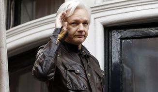 In this May 19, 2017 file photo, WikiLeaks founder Julian Assange greets supporters from a balcony of the Ecuadorian embassy in London. (AP Photo/Frank Augstein)