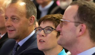 FILE - In this Wednesday, Nov. 21, 2018 file photo Friedrich Merz, former CDU faction leader, left, Annegret Kramp-Karrenbauer, General Secretary of the German Christian Democratic Union, and Germany's Health Minister Jens Spahn, right, all members of the German Christian Democratic Party, attend a CDU regional conference and present their concepts as candidates for the CDU chairmanship in Seebach, central Germany, Wednesday. Three high-profile contenders are vying to lead Angela Merkel's party as the longtime German chancellor makes way after 18 years for a successor who could shape the European Union's most populous country for the next generation. The center-right Christian Democratic Union will elect on Friday a new chairman or chairwoman, who will be the favorite to run for chancellor in Germany's next election. (AP Photo/Jens Meyer, file)