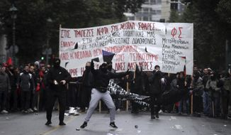 Hooded youths gesture at riot police in Athens, on Thursday, Dec. 6, 2018 during a rally commemorating the killing of a 15-year old student back in 2008. Hundreds of school and university students march through the streets of the Greek capital to mark the tenth anniversary of a fatal police shooting of a teenager in Athens that sparked the worst rioting Greece had seen in decades. (AP Photo/Petros Giannakouris)