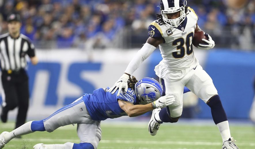 FILE - In this Sunday, Dec. 2, 2018, file photo, Los Angeles Rams running back Todd Gurley (30) pulls away from Detroit Lions defensive back Mike Ford during the first half of an NFL football game in Detroit. Gurley finds himself in exclusive company. He has gained 1,649 yards from scrimmage and scored 19 TDs so far this season. Only six players have topped those marks in the first 12 games. (AP Photo/Rey Del Rio, File)