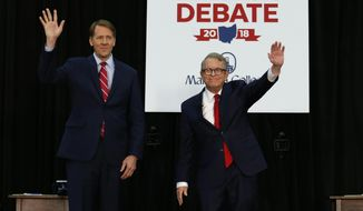 FILE - In this Oct. 1, 2018, file photo, Democratic gubernatorial candidate Richard Cordray, left, and Ohio Attorney General and Republican gubernatorial candidate Mike DeWine wave to the crowd before a debate at Marietta College in Marietta, Ohio. A third party contending it was unfairly excluded from a fledgling debate series in Ohio's 2018 governor's race is about to air its claims before state election regulators. The Ohio Elections Commission is hearing the Libertarian Party of Ohio's case Thursday, Dec. 6. (AP Photo/Paul Vernon, Pool, File)