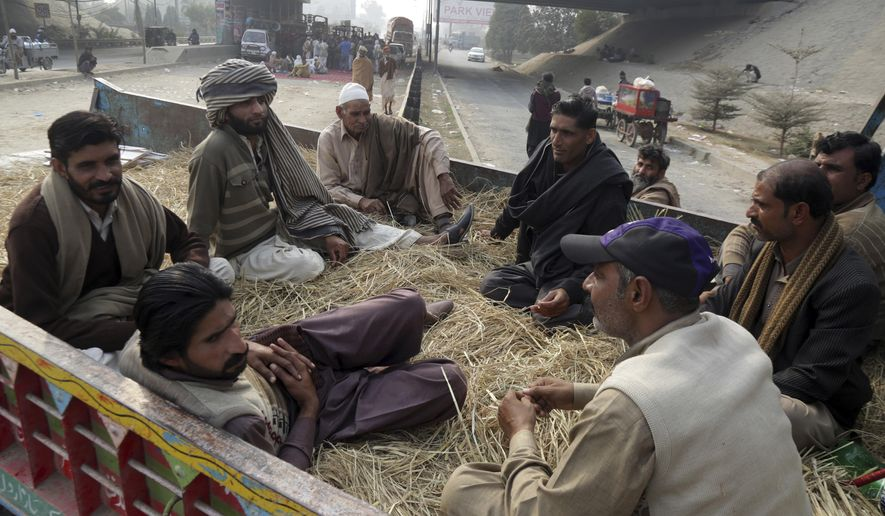 Pakistani farmers block a main road during a sit-in-protest in Lahore, Pakistan, Thursday, Dec. 6, 2018. Hundreds of farmers rallied in eastern city Lahore to demand a decrease in the prices of fertilizers, pesticides and seeds, and to pressure authorities so they could get higher prices for sugarcane and other produce. (AP Photo/K.M. Chaudary)