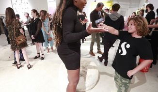 In this, Wednesday, Dec. 5, 2018 photo, Lucas Bacardi-Shriftman, 10, takes a go at interviewing tennis player Serena Williams during the launch of her first pop-up shop at the Faena Bazaar in Miami Beach, Fla. The 23-time Grand Slam champion not only designed all the clothing in the shop, but also painted all the art on walls, calling painting her outlet. (AP Photo/Wilfredo Lee)