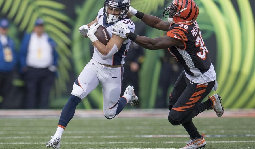 FILE - In this Sunday, Dec. 2, 2018, file photo, Denver Broncos running back Phillip Lindsay (30) is tackled by Cincinnati Bengals strong safety Shawn Williams (36) during the first half of the NFL football game in Cincinnati. A terrific trio of rookies, including Lindsay, have led a turnaround from a 3-6 start to help Denver win three straight and get into the playoff picture. (AP Photo/Bryan Woolston, File)